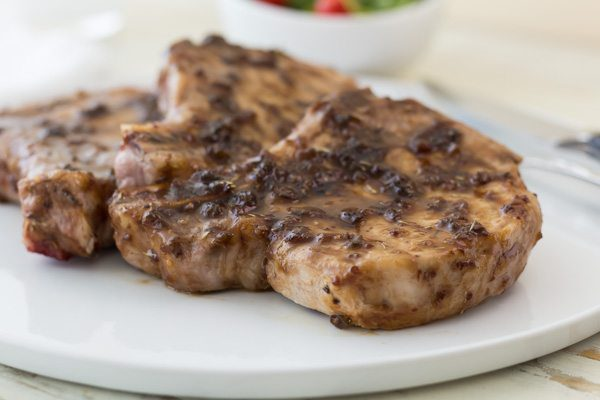 pork chops on a white place with raspberry jalapeno glaze