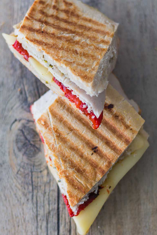 Smoked Turkey Artichoke Panini sandwich tastes as good as it looks. Made with ciabatta sandwich roll spread with Artichoke Parmesan Tapenade, stacked with roasted red pepper, smoked turkey and topped with mozzarella cheese. Spoonabilities.com