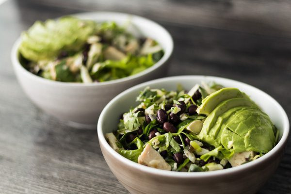 Two white bowls of summer salad full of avocado, black beans, chicken, cilantro and manchego cheese.