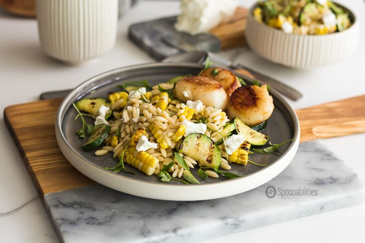 Grilled Corn Zucchini Orzo Salad with a perfect buttery seared scallop, topped with a tangy goat cheese and fresh cilantro micro greens. Spoonabilities.com