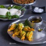 Fresh Stuffed Squash Blossoms is a unique appetizer, filled with creamy burrata and Kalamata olive and oregano spread. Delicious light and easy recipe. Spoonabilities.com