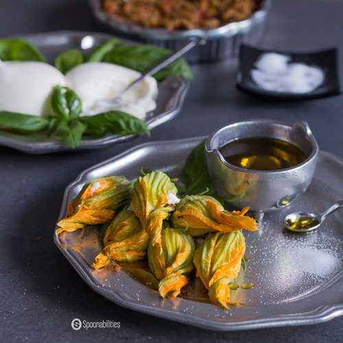 Fresh Stuffed Squash Blossoms is a unique appetizer, filled with creamy burrata and black olive tapenade. Delicious light and easy recipe. Spoonabilities.com
