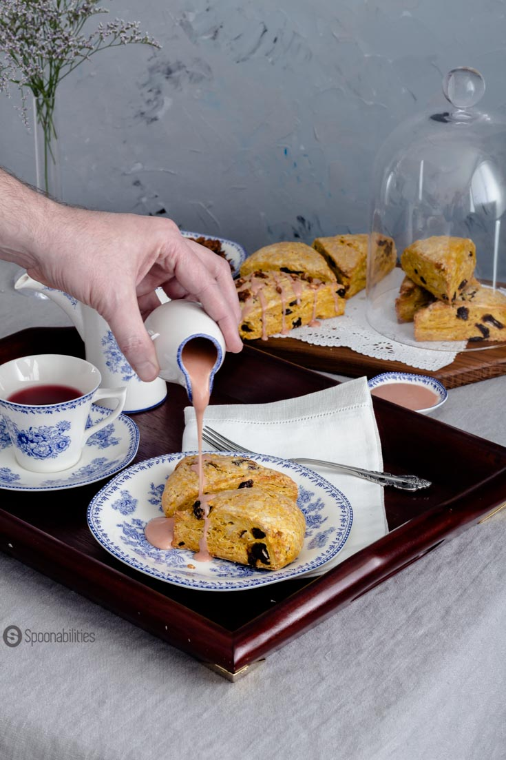 Moist, soft and crumbly Cherry Pumpkin Scones with a drizzle of blood orange & maple syrup glaze and garnished with roasted pumpkin seeds. Spoonabilities.com