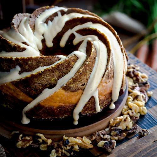 Pumpkin Carrot Bundt Cake filled with a layer of cheesecake for a moist, rich cake. Fall inspired dessert with pumpkin spice cream cheese drizzle. Spoonabilities.com