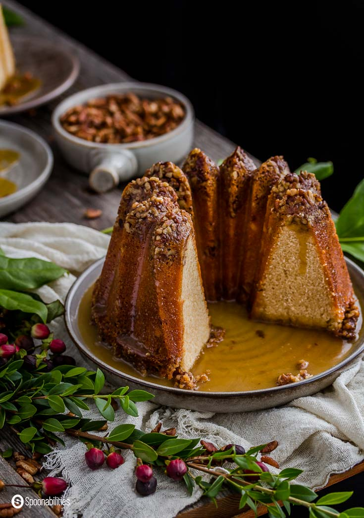 Pecan Pie Bundt Cake is luscious and rich dessert. The cake is so moist and delicious with a crown of decedent pecans lining the top of tall towers of a cake. Spoonabilities.com
