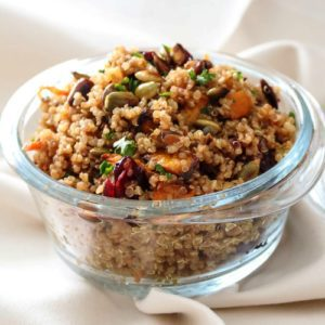 Quinoa Salad with Roasted Butternut Squash and Pumpkin Honey Mustard Vinaigrette in a glass bowl. This recipe is great as a side dish for all your meals, or for lunch, or a full main dinner dish. Spoonabilities.com