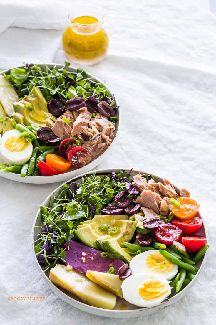 Two bowls of Nicoise Salad on a gray tablecloth with a glass salad dressing pitcher of Dijon mustard vinaigrette