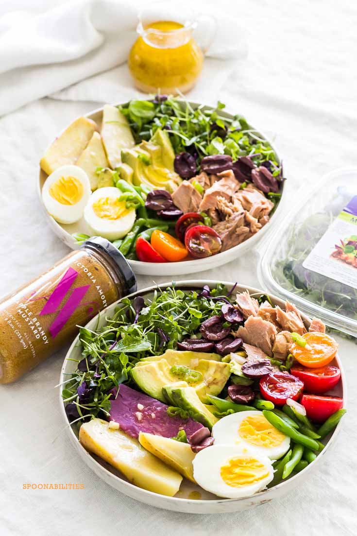 Two bowls of Nicoise Salad on a gray tablecloth with a glass salad dressing pitcher of vinaigrette and a jar of Apple Brandy Mustard.