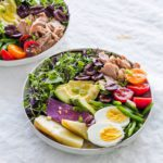 Two bowls of Classic Nicoise Salad on a gray tablecloth