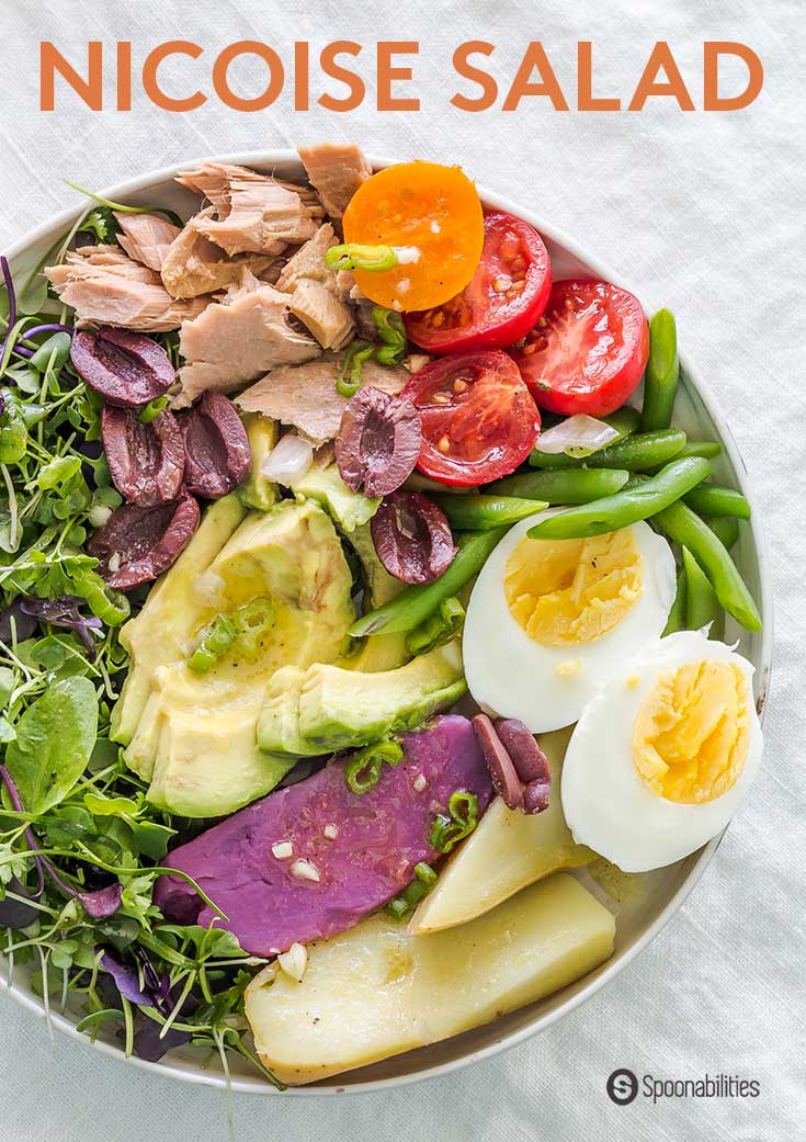 Dinner bowl of Classic Nicoise Salad with tuna, potatoes, green beans, eggs and microgreens, and a salad dressing of apple brandy mustard vinaigrette.