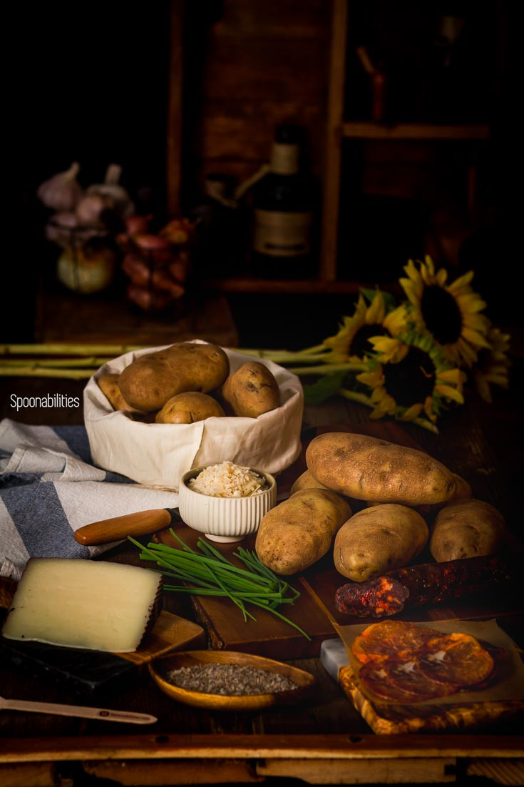 Wooden table filled with Spanish ingredients of chorizo & Lomo Iberico, Manchego cheese & aioli, preparing to make Spanish style baked potatoes. Spoonabilities.com