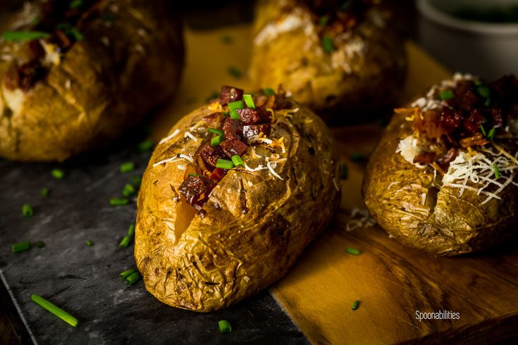 Close up of a baked potato with a perfectly crispy skin and creamy, fluffy interior. Spanish flavor from the aioli, manchego cheese and chorizo & Lomo Iberico. Spoonabilities.com