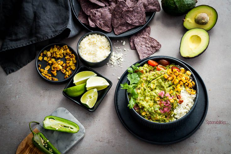 The best guacamole recipe presented in a black round bowl and served with blue corn tortillas Spoonabilities.com