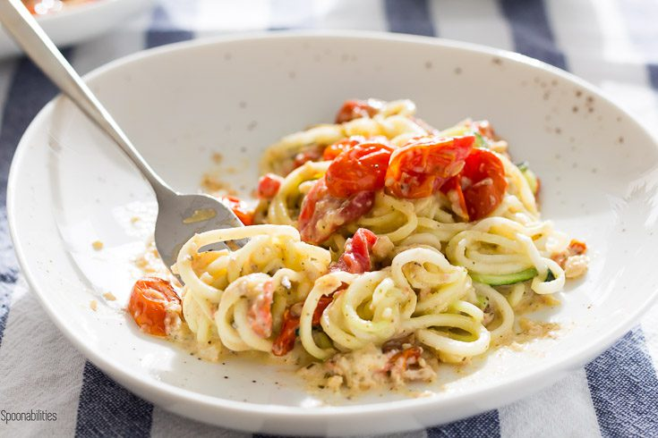 Plate with Zucchini noodles is a healthy summer zoodle recipe with flavorful lemon artichoke pesto, roasted cherry tomatoes & asiago cheese. Spoonabilities.com