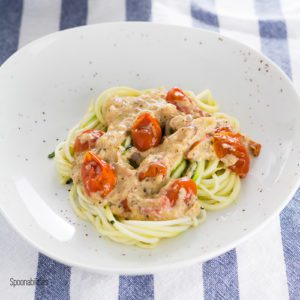 A plate with a Mediterranean flavor inspired Zucchini Noodles (zoodles) with artichoke lemon pesto & roasted cherry tomatoes. A healthy recipe is full of flavor; quick and easy to make in under 30 minutes. Spoonabilities.com