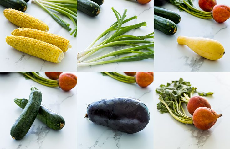 Whole vegetables in a counter top like corn, green onions, zucchini, yellow squash, yellow beets and eggplant. Spoonabilities.com