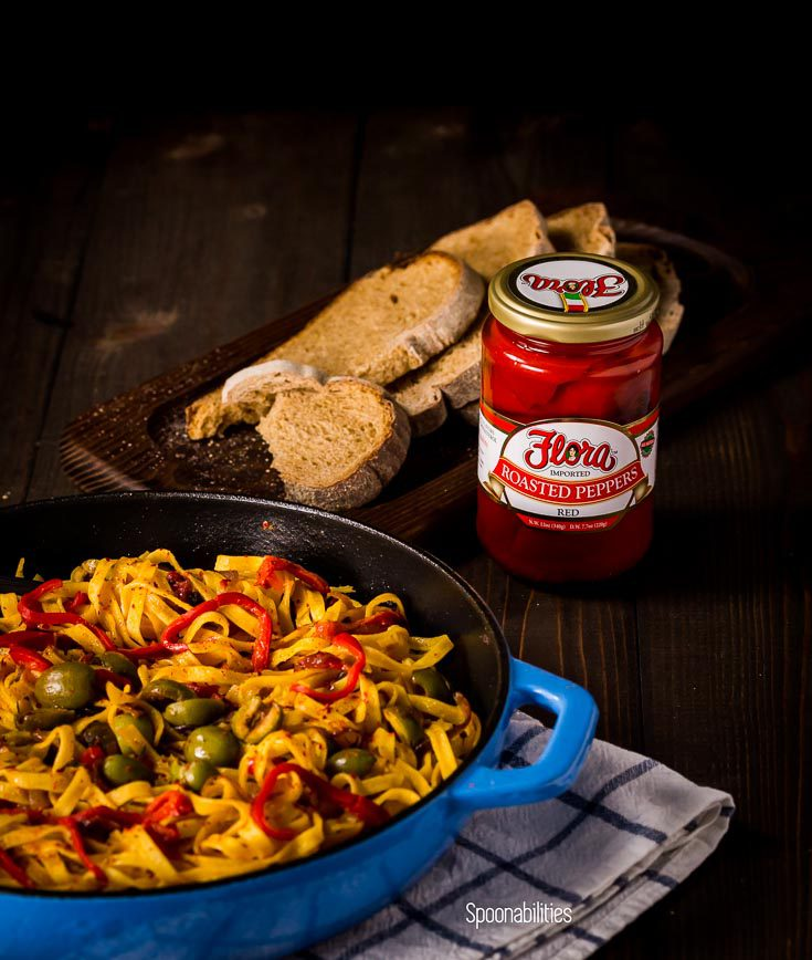Blue skillet with Roasted Red pepper pasta next to a jar of roasted red pepper by Flora fine Foods. Spoonabilities.com
