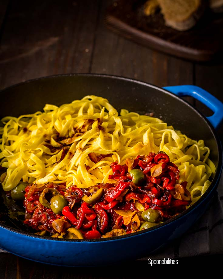 Blue cast iron skillet with roasted red pepper & Sicilian olives with Egg Tagliatelle pasta. Spoonabilities.com