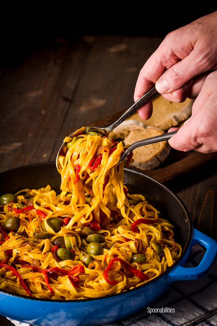 Serving the Roasted Red Pepper Pasta with Sicilian Olives in blue cast iron skillet. Spoonabilities.com