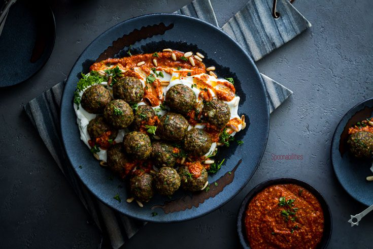 Large plate with Lamb meatballs are perfect as an appetizer or as a main dish. Served in a bed of Greek yogurt and a Piquillo pepper pesto. Spoonabilities.com