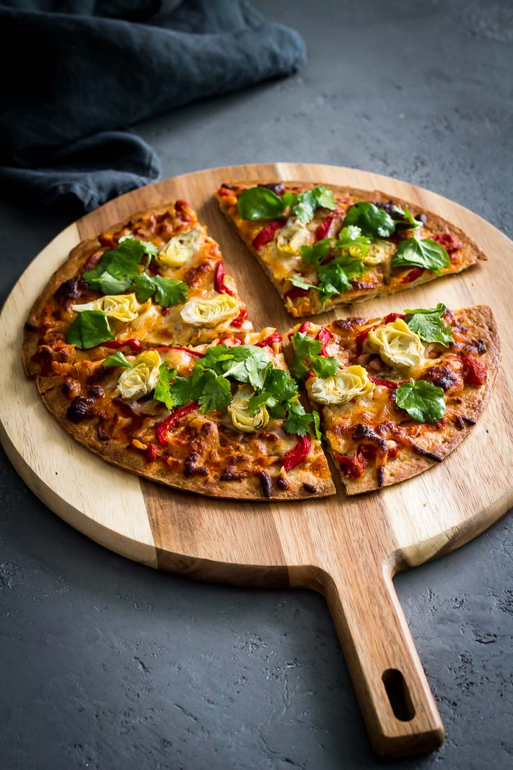 Cauliflower Crust Pizza with Artichokes and Roasted Red Pepper in a wooden board. Spoonabilities.com