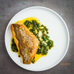 Round white plate with Crispy-Skinned Snapper with Caper Salsa. This salsa has fresh parsley, chili paste, cilantro, olive oil and lemon juice. Spoonabilities.com
