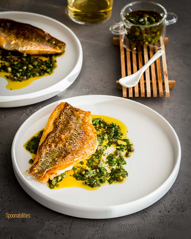 Two white plates with crispy skin snapper with caper salsa. Spoonabilities.com
