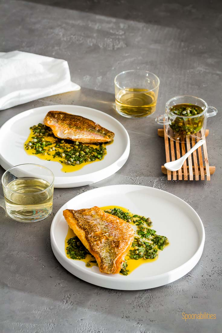 Two round white plates with Crispy Skin Snapper with Caper sauce in a small glass bowl. Two glasses of white wine. Spoonabilities.com