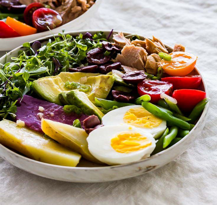 Large bowl of Nicoise Salad with mild cayenne Dijon mustard vinaigrette, on a gray tablecloth