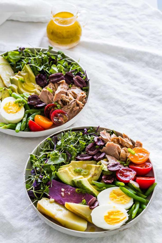 Nicoise Salad in two bowls on a gray tablecloth with a glass salad dressing pitcher of mild cayenne Dijon mustard vinaigrette