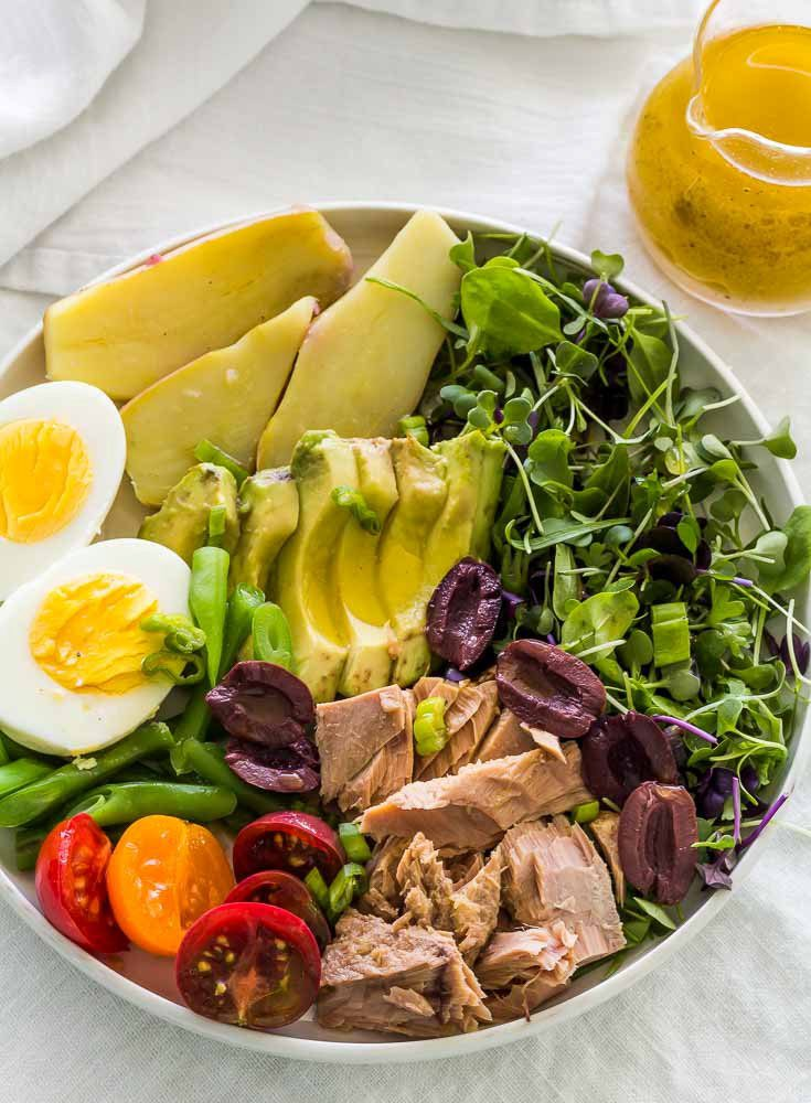 Large bowl of Nicoise Salad with glass pitcher of Dijon mustard vinaigrette, on a gray tablecloth