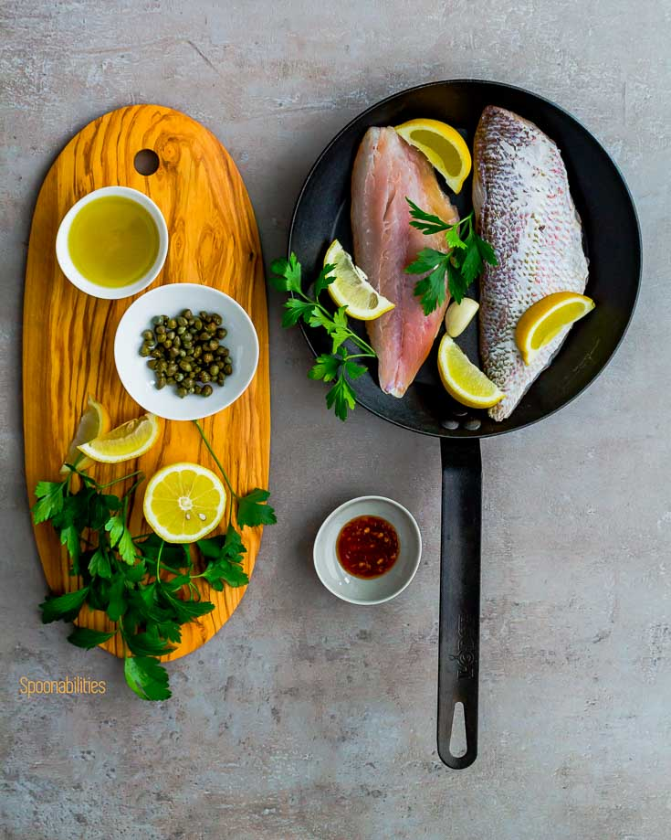 Raw Snapper fish in a fry pan next to a wooden board with capers, lemon, flat parsley, olive oil & Chili paste. Spoonabilities.com
