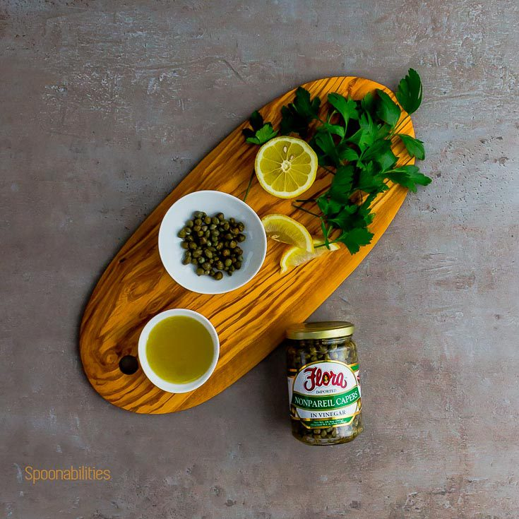 Wooden board with parsley, lemon, olive oil and Capers by Flora Fine Foods. Spoonabilities