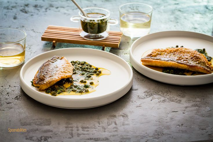 Two round white plates with crispy skin Snapper with two glasses of wine and caper salsa in a small glass bowl. Spoonabilities.com