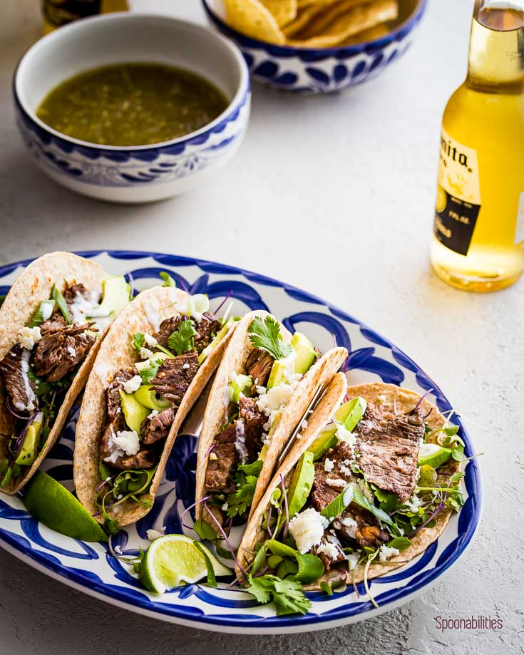 Juicy and tender grilled Skirt Steak Tacos on a oval serving plate and a beer. Spoonabilities.com