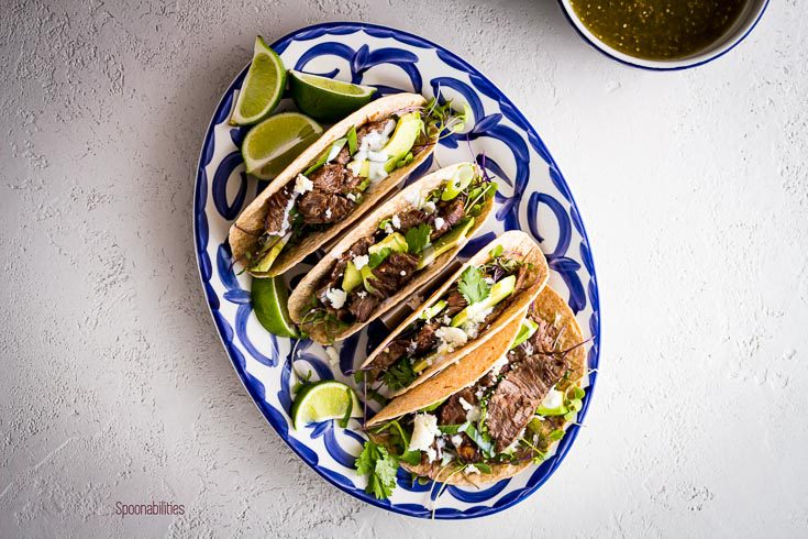 Overhead photo with four Skirt steak tacos in a oval plate and in a small bowl tomatillo salsa. Spoonabilities.com