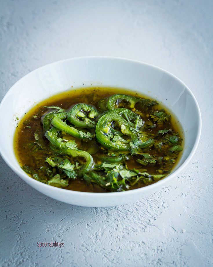 Jalapeño lime Marinade with extra virgin olive oil, cilantro and garlic in a small bowl. Spoonabilities.com