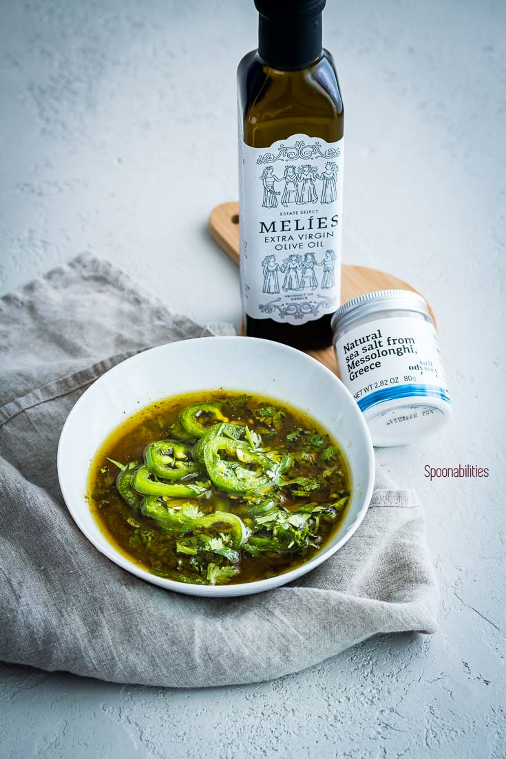 Jalapeño Lime marinade in a small bowl next to a bottle of Melies extra virgin olive oil and Greek sea salt. Spoonabilities.com
