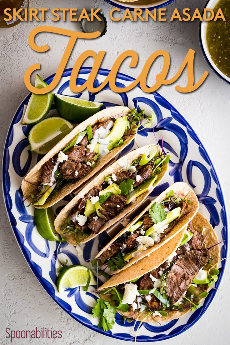 Blue and white oval plate of four Skirt Steak Tacos - Carne Asada Tacos with lime wedges Spoonabilities