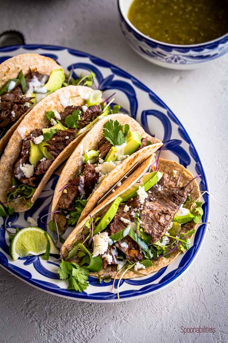 Close up Skirt steak tacos in a white and blue oval plate and in the back a small bowl with tomatillo salsa. Spoonabilities.com