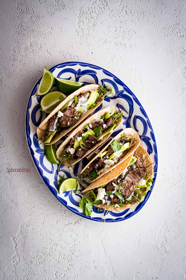 Oval serving plate in the center with four skirt steak tacos and garnish with lime. Spoonabilities.com