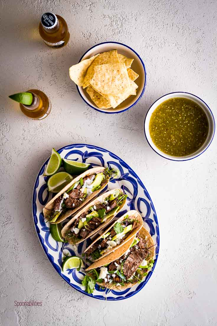 Flat lay photo with an oval serving plate with four skirt steak tacos and two small bowls with chips and tomatillo salsa. Spoonabilities.com