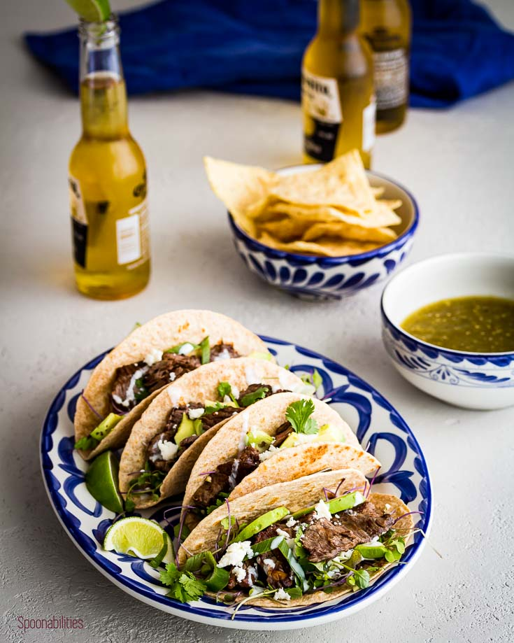 Oval serving plate with four Skirt steak tacos and three beers in the background. spoonabilities.com