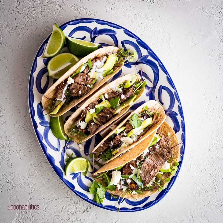 Juicy and tender grilled Skirt Steak Tacos topped with avocado, cilantro, queso fresco, and sour cream. Spoonabilities.com