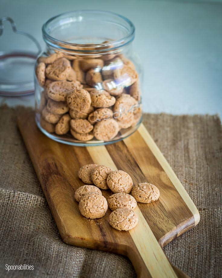 Amaretti cookies in a jar on top of a wooden board with some Amaretti cookies. Spoonabilities.com