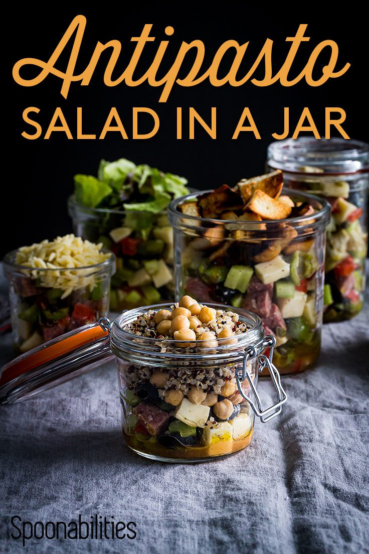 Small glass jar without the lid in the front with Antipasto salad with chickpeas and quinoa and in the background four more jars with salad. Spoonabilities.com