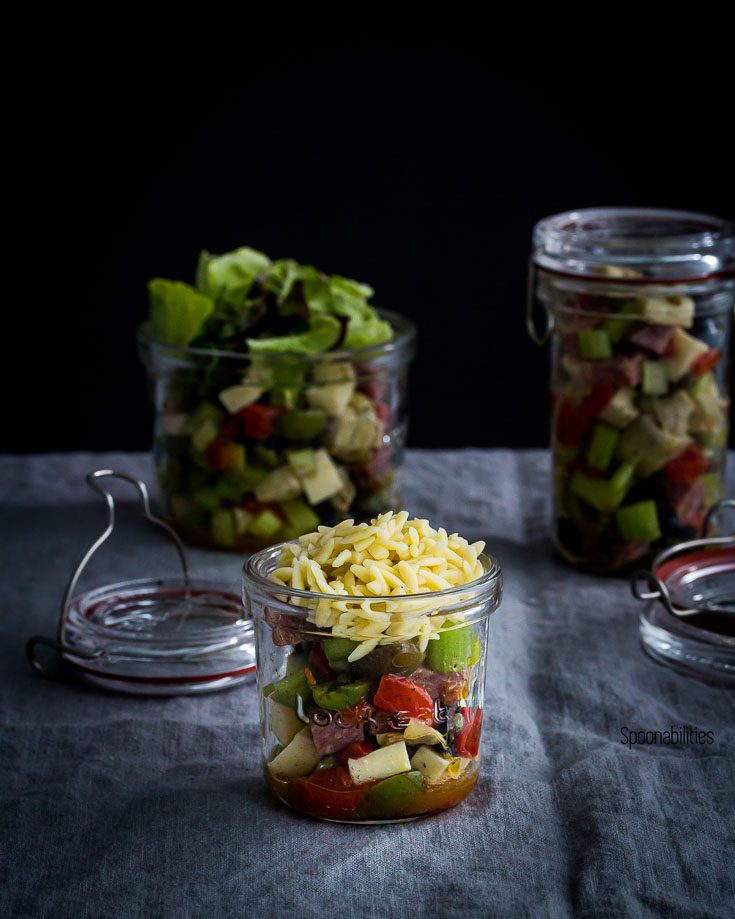 Small glass jar with Antipasto orzo salad and two jars with salad in the background. Spoonabilities.com