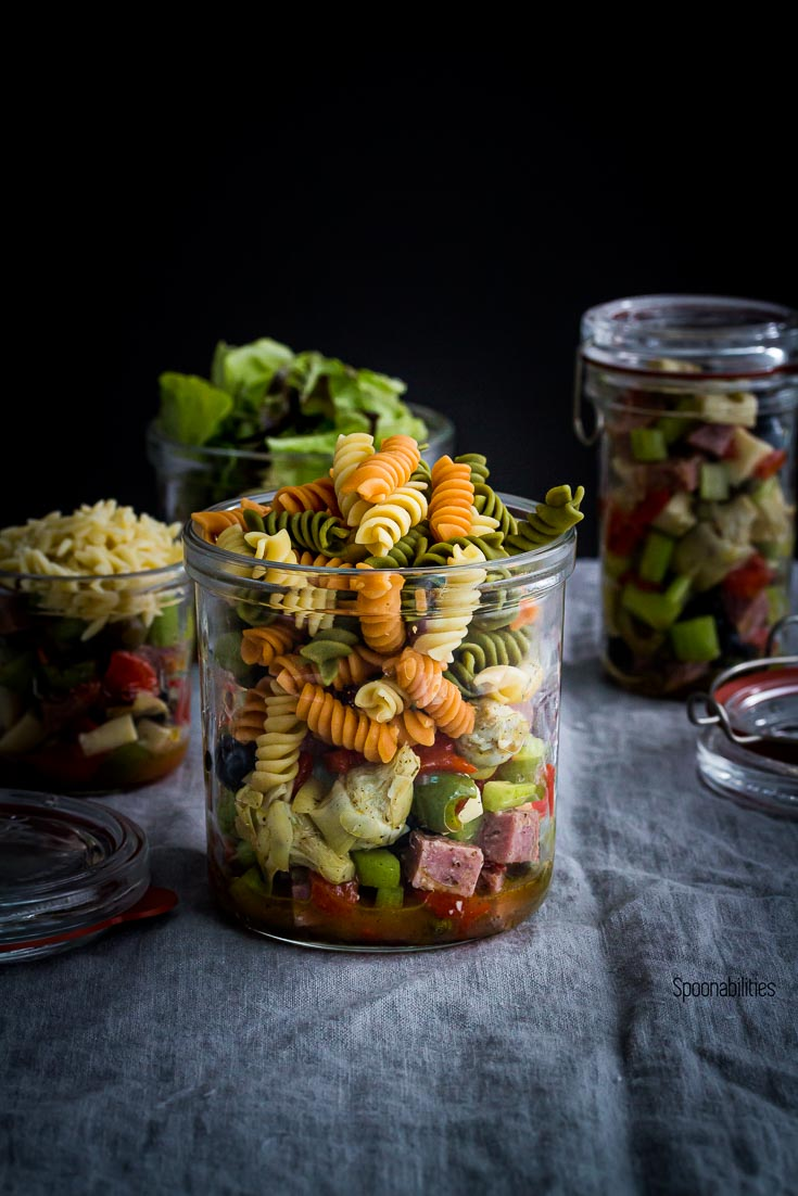 A Jar with Antipasto Pasta Salad and three jars in the background with salad. Spoonabilities.com
