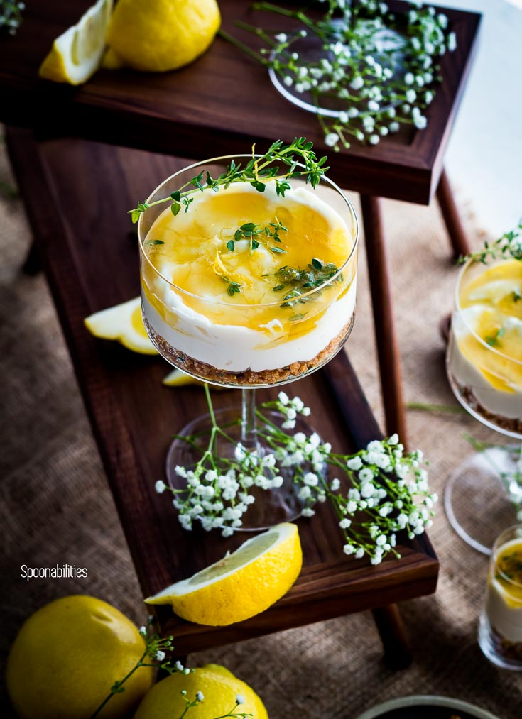 No-Bake Cheesecake in a cocktail glass garnished with a thyme lemon herb. Spoonabilities.com