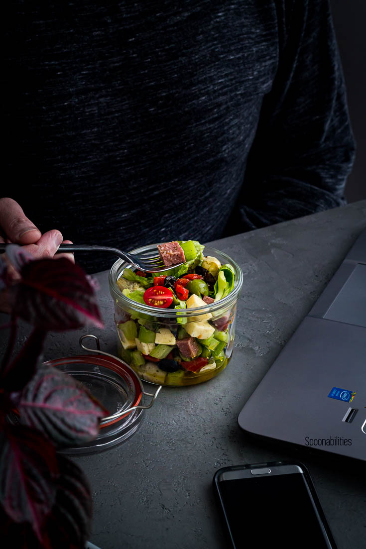 A guy eating salad in a jar with antipasto and lettuce next to his laptop. Spoonabilities.com